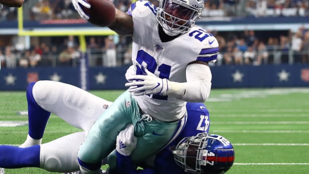 Sep 8, 2019; Arlington, TX, USA; Dallas Cowboys running back Ezekiel Elliott (21) reaches for the goal line for a touchdown in the third quarter against New York Giants linebacker Alec Ogletree (47) at AT&T Stadium.