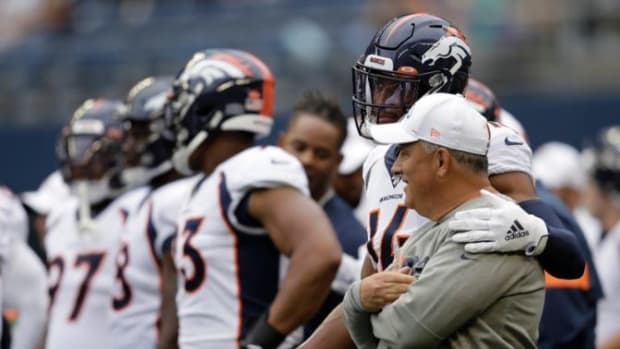 Denver Broncos wide receiver Courtland Sutton (14) stands with coach Vic Fangio, right, before the team's NFL football preseason game against the Seattle Seahawks in Seattle. While everyone else was zigging, general manager John Elway was zagging, hiring a 61-year-old defensive minded head coach in Fangio while other teams searched for the next offensive guru.