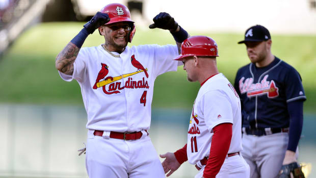 Oct 7, 2019; St. Louis, MO, USA; St. Louis Cardinals catcher Yadier Molina (4) celebrates with first base coach Stubby Clapp (11) after hitting an RBI single in the eighth inning against the Atlanta Braves in game four of the 2019 NLDS playoff baseball series at Busch Stadium. Mandatory Credit: Jeff Curry-USA TODAY Sports