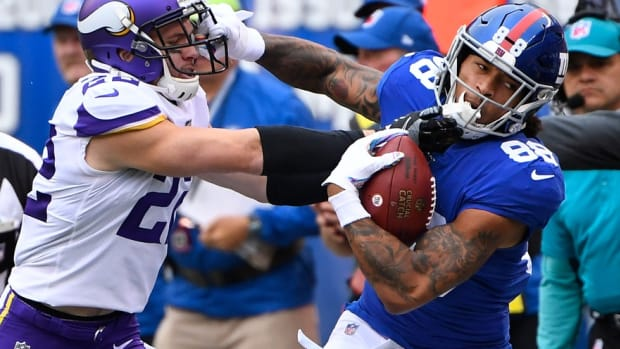 Oct 6, 2019; East Rutherford, NJ, USA; New York Giants tight end Evan Engram (88) gets a first down in the first quarter as Minnesota Vikings free safety Harrison Smith (22) defends at MetLife Stadium.