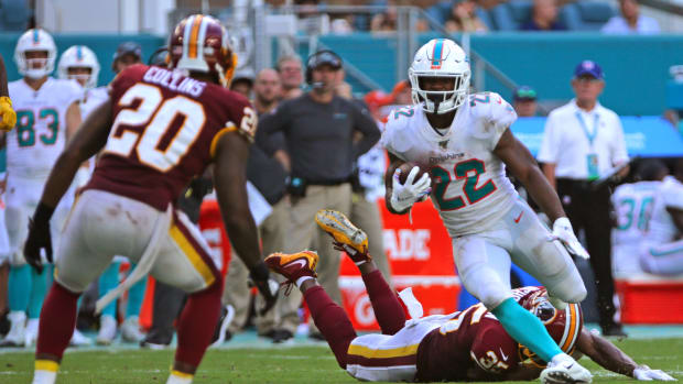 Oct 13, 2019; Miami Gardens, FL, USA; Miami Dolphins running back Mark Walton (22) carries the ball and avoids a tackle by Washington Redskins strong safety Montae Nicholson (35) in the fourth quarter of the game at Hard Rock Stadium. Mandatory Credit: Sam Navarro-USA TODAY Sports