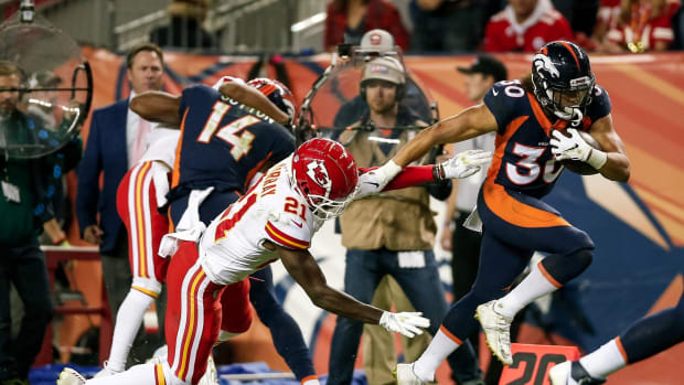 Denver Broncos running back Phillip Lindsay (30) avoids the tackle of Kansas City Chiefs defensive back Eric Murray (21) in the third quarter at Broncos Stadium at Mile High.
