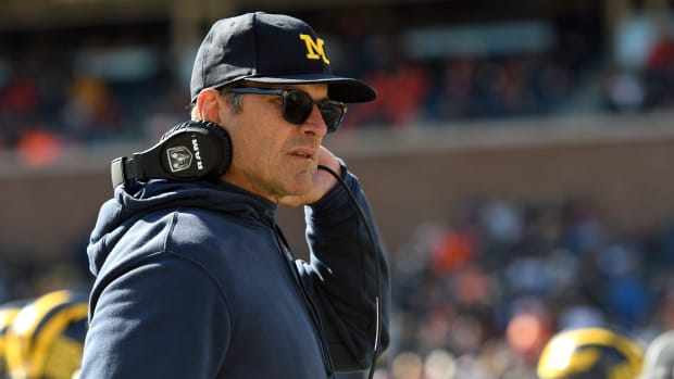 Michigan Wolverines head coach Jim Harbaugh removes his headset during the second half of the game against the Illinois Fighting Illini.