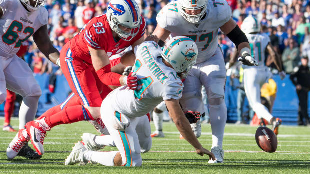 Oct 20, 2019; Orchard Park, NY, USA; Miami Dolphins quarterback Ryan Fitzpatrick (14) fumbles the ball as Buffalo Bills defensive end Trent Murphy (93) and offensive guard Jesse Davis (77) go for the ball in the fourth quarter at New Era Field. Mandatory Credit: Mark Konezny-USA TODAY Sports