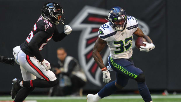 Seattle Seahawks running back Chris Carson (32) runs against Atlanta Falcons cornerback Isaiah Oliver (26) during the first quarter at Mercedes-Benz Stadium. Mandatory Credit: Dale Zanine-USA TODAY Sports