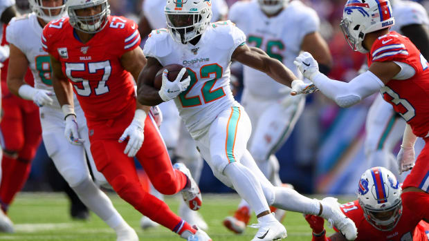 Oct 20, 2019; Orchard Park, NY, USA; Miami Dolphins running back Mark Walton (22) runs with the ball in front of Buffalo Bills outside linebacker Lorenzo Alexander (57) during the first quarter at New Era Field. Mandatory Credit: Rich Barnes-USA TODAY Sports
