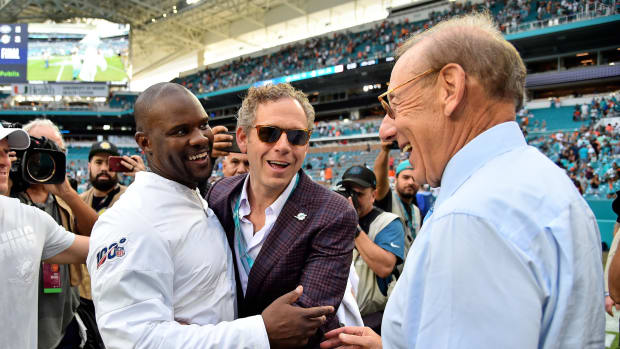 Coach Brian Flores is congratulated by Dolphins owner Steve Ross after his first win for Miami against the Jets.