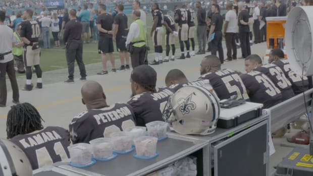 Group of Saints Players Sit During National Anthem - IMAGE