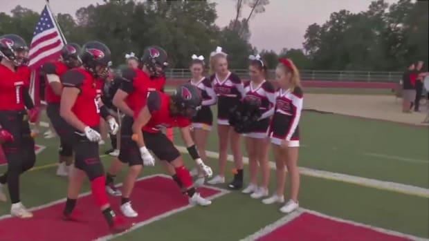 High school cheerleader battling cancer receives support from football team - IMAGE