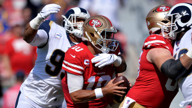 Oct 13, 2019; Los Angeles, CA, USA; San Francisco 49ers quarterback Jimmy Garoppolo (10) is sacked by Los Angeles Rams defensive tackle Aaron Donald (left) during the first quarter at Los Angeles Memorial Coliseum. Mandatory Credit: Orlando Ramirez-USA TODAY Sports