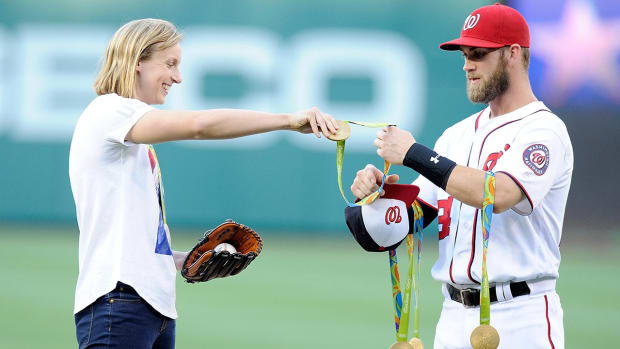 Katie Ledecky throws out first pitch at Nationals game, Bryce Harper holds her medals - IMAGE