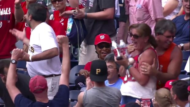 A Whole New Approach: Fan catches foul ball with two drinks in hands IMAGE
