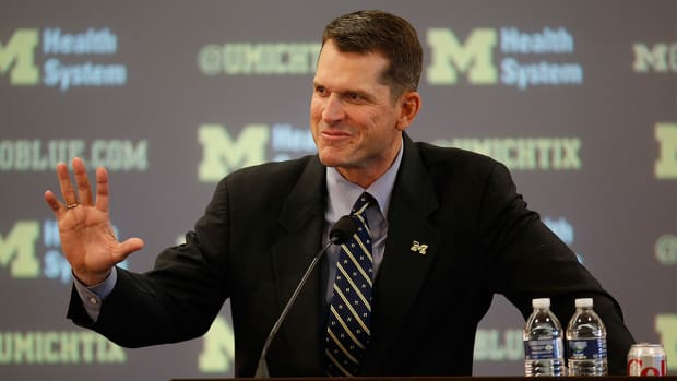Michigan head coach Jim Harbaugh defends satellite camps