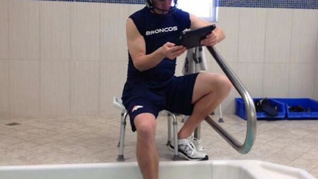 peyton manning soaking foot looking at ipad.jpg