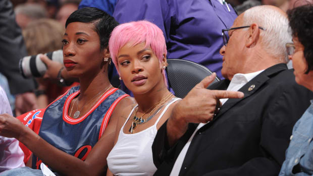 Rihanna at a basketball game with pink hair