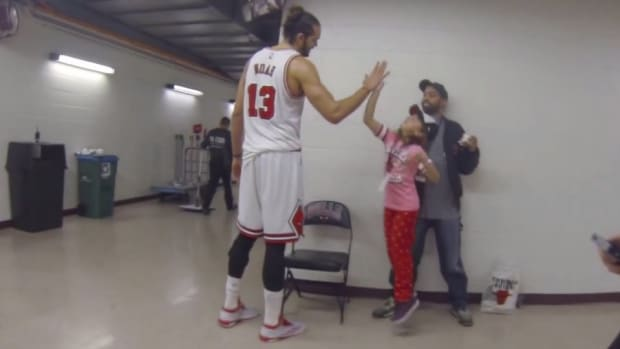 Chicago Bulls Joakim Noah gives young fan a high five