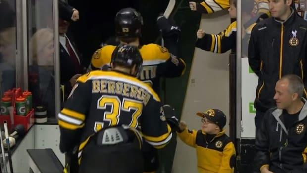 Boston Bruins fan fist bumps the whole team