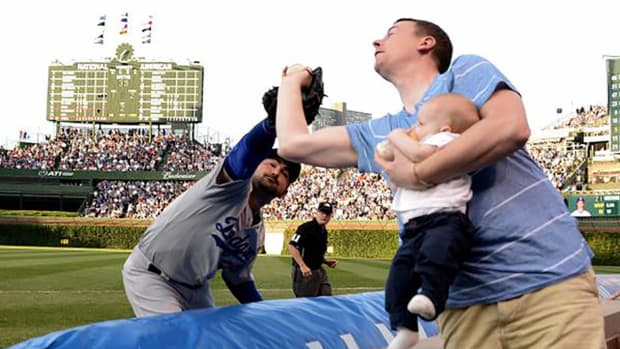 Fan at Wrigley Field snags foul ball while holding baby IMAGE