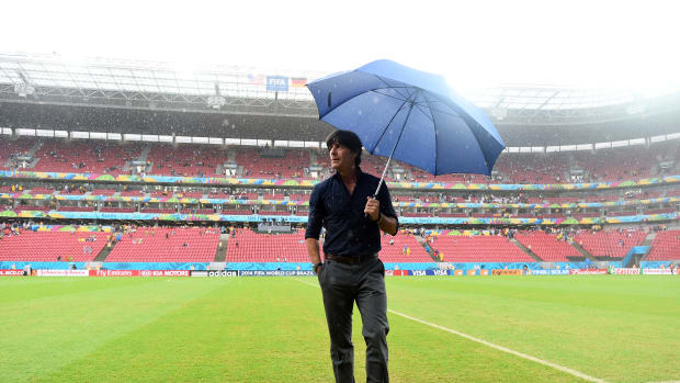 German soccer coach looks at Recife field in rain holding umbrella