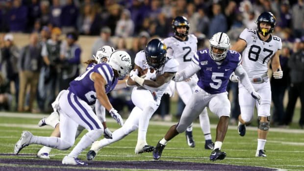 West Virginia Mountaineers running back Leddie Brown (4) is tackled by Kansas State Wildcats linebacker Da'Quan Patton (5) and defensive back Denzel Goolsby (20) during the fourth quarter of a game at Bill Snyder Family Stadium