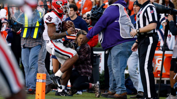 Georgia running back Brian Herrien collides with photographer Chamberlain Smith
