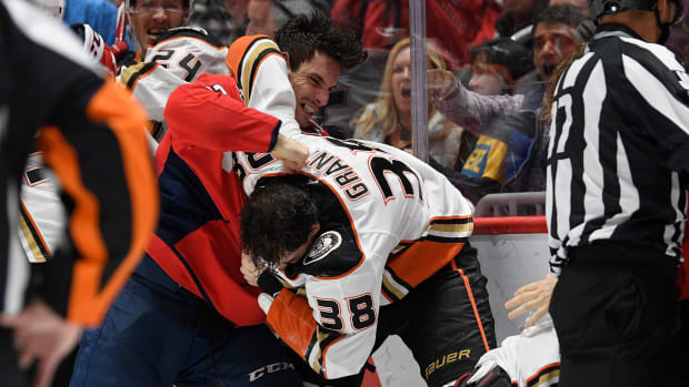 Capitals' Garnet Hathaway and Ducks' Derek Grant fight during an NHL game.
