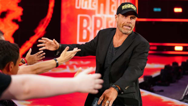 WWE's Shawn Michaels makes his entrance wearing an NXT hat.