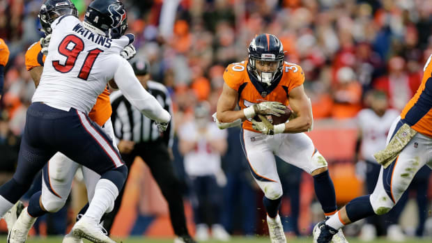 Denver Broncos offensive tackle Elijah Wilkinson (68) defends against Houston Texans defensive end Carlos Watkins (91) as running back Phillip Lindsay (30) runs the ball in the third quarter at Broncos Stadium at Mile High.