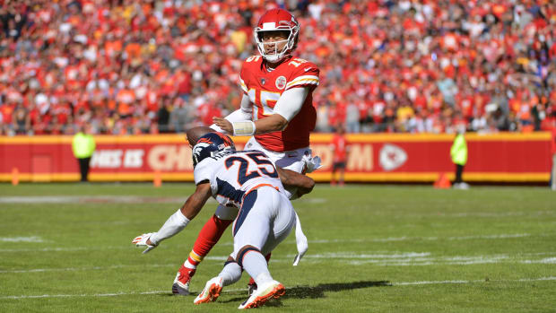 Kansas City Chiefs quarterback Patrick Mahomes (15) is tackled by Denver Broncos cornerback Chris Harris (25) during the first half at Arrowhead Stadium.