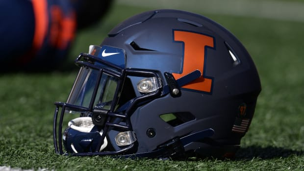 Illinois Fighting Illini helmet sits on the field as players stretch before the start of the game between the Illinois Fighting Illini and the Michigan Wolverines at Memorial Stadium.