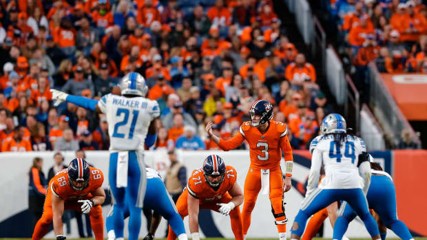 Denver Broncos quarterback Drew Lock (3) motions at the line of scrimmage behind offensive guard Austin Schlottmann (71) and offensive tackle Jake Rodgers (69) as Detroit Lions linebacker Jalen Reeves-Maybin (44) and free safety Tracy Walker (21) look on in the fourth quarter at Empower Field at Mile High.