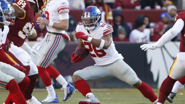 Dec 22, 2019; Landover, Maryland, USA; New York Giants running back Saquon Barkley (26) carries the ball past Washington Redskins nose tackle Daron Payne (94) in the second quarter at FedEx Field.