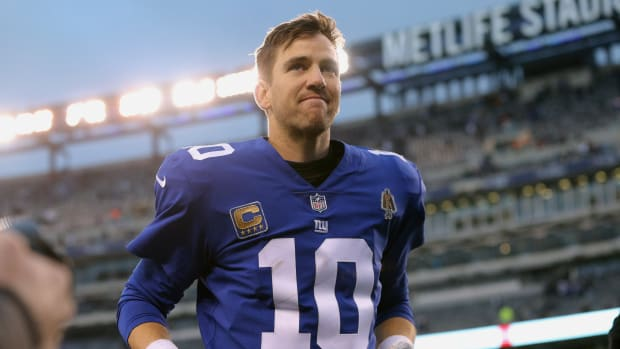 Giants QB Eli Manning runs off the field without his helmet on
