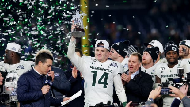 Dec 27, 2019; Bronx, New York, USA; Michigan State quarterback Brian Lewerke (14) holds up the MVP trophy after defeating the Wake Forest Demon Deacons in the Pinstripe Bowl at Yankee Stadium. Mandatory Credit: Brad Penner-USA TODAY Sports