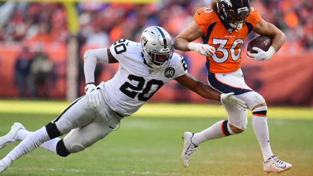 Denver Broncos running back Phillip Lindsay (30) carries past Oakland Raiders cornerback Daryl Worley (20) in the second quarter at Empower Field at Mile High.