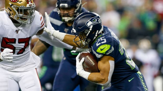 Seattle Seahawks running back Travis Homer (25) stiff-arms San Francisco 49ers linebacker Dre Greenlaw (57) on a rushing attempt during the first quarter at CenturyLink Field.