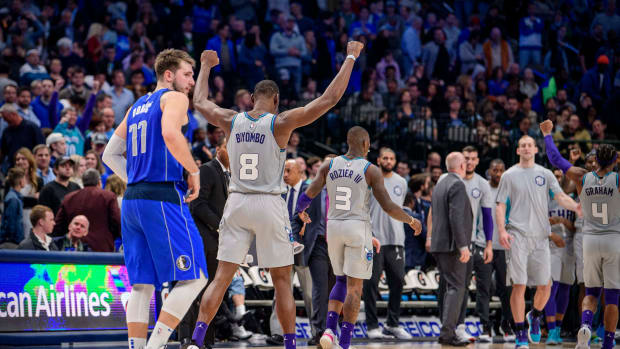 Jan 4, 2020; Dallas, Texas, USA; Charlotte Hornets center Bismack Biyombo (8) celebrates the win as Dallas Mavericks forward Luka Doncic (77) walks off the court after the game at the American Airlines Center. Mandatory Credit: Jerome Miron-USA TODAY Sports