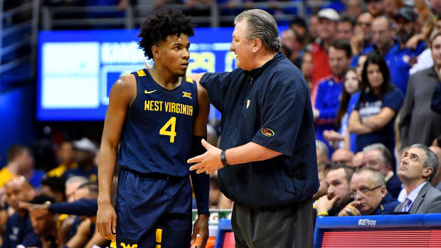 West Virginia Mountaineers head coach Bob Huggins (right) talks with guard Miles McBride (4) during a timeout during the second half against the Kansas Jayhawks at Allen Fieldhouse.