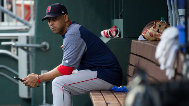 Alex Cora looks onto the field from the Red Sox dugout at Fenway Park.