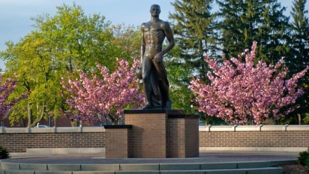 Sunrise hightlights spring blossoms behind the Spartan statue. (PHOTO:  MSU SID)