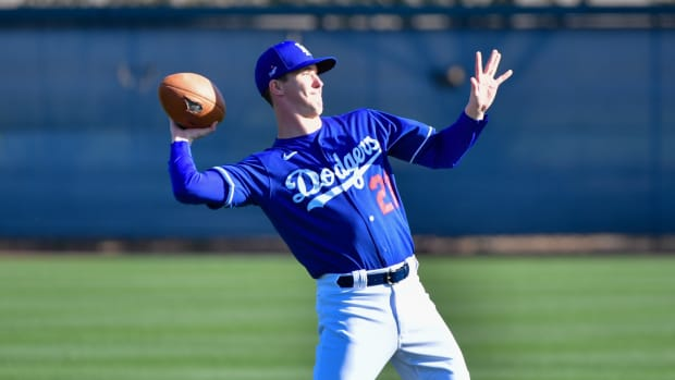Feb 18, 2020; Glendale, Arizona, USA; Los Angeles Dodgers starting pitcher Walker Buehler (21) throws a football during a spring training workout at Camelback Ranch. Mandatory Credit: Matt Kartozian-USA TODAY Sports