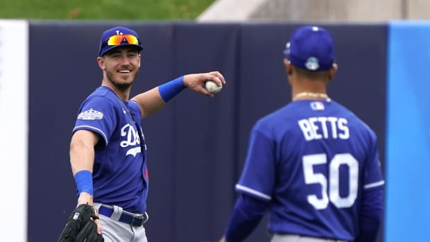 Feb 28, 2020; Phoenix, Arizona, USA; Los Angeles Dodgers center fielder Cody Bellinger (35) and Mookie Betts (50) warm up in between innings against the Milwaukee Brewers during a spring training game at American Family Fields of Phoenix. Mandatory Credit: Rick Scuteri-USA TODAY Sports