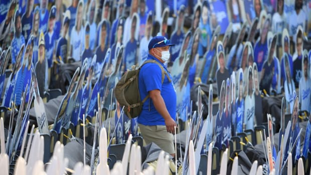 Jul 26, 2020; Los Angeles, California, USA; A grounds crew member makes his way through a maze of fan cut outs before the game between the Los Angeles Dodgers and the San Francisco Giants at Dodger Stadium. Mandatory Credit: Jayne Kamin-Oncea-USA TODAY Sports
