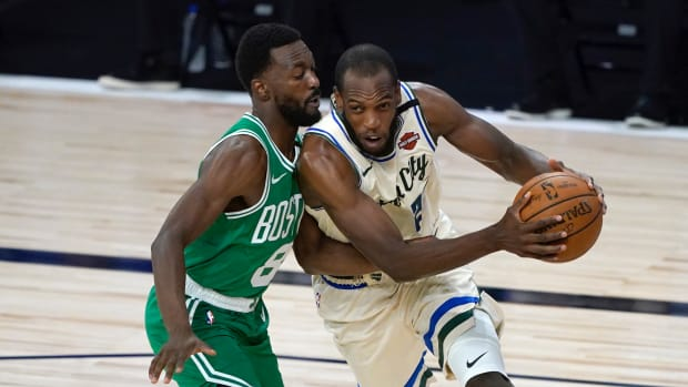 Milwaukee Bucks' Khris Middleton, right, heads to the basket past Boston Celtics' Kemba Walker during the first half of an NBA basketball game Friday, July 31, 2020, in Lake Buena Vista, Fla.
