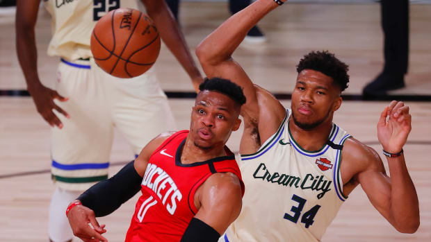 Russell Westbrook #0 of the Houston Rockets passes under pressure from Giannis Antetokounmpo #34 of the Milwaukee Bucks