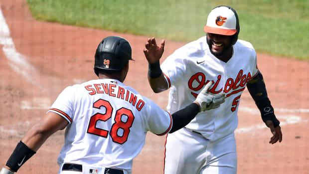 Baltimore Orioles second baseman Hanser Alberto (57) high fives catcher Pedro Severino (28) after scoring a run