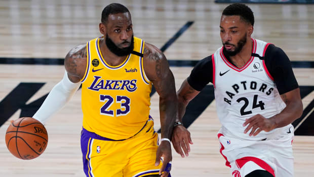 Los Angeles Lakers forward LeBron James handles the ball against Toronto Raptors guard Norman Powell