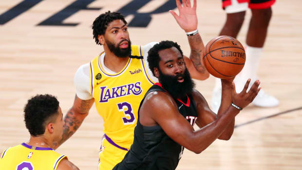 Houston Rockets guard James Harden (13) passes the ball between Los Angeles Lakers forward Kyle Kuzma (0) and forward Anthony Davis (3) during the second half of an NBA basketball game at The Arena.