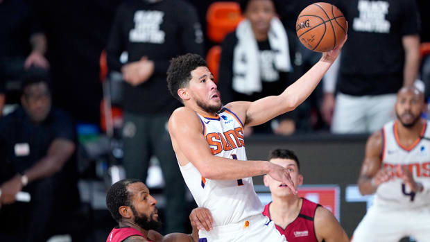 Aug 8, 2020; Lake Buena Vista, Florida, USA; Phoenix Suns' Devin Booker (1) goes to the basket over Miami Heat's Andre Iguodala, left, and Tyler Herro, right, during the second half of an NBA basketball game at Visa Athletic Center.
