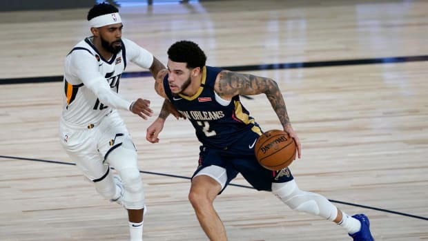 New Orleans Pelicans' Lonzo Ball (2) heads to the basket past Utah Jazz's Mike Conley during the second half of an NBA basketball game.